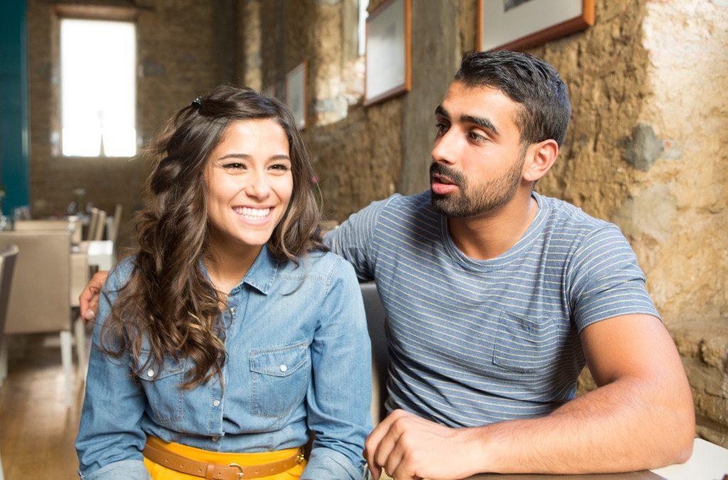 Young couple talking at car dealership