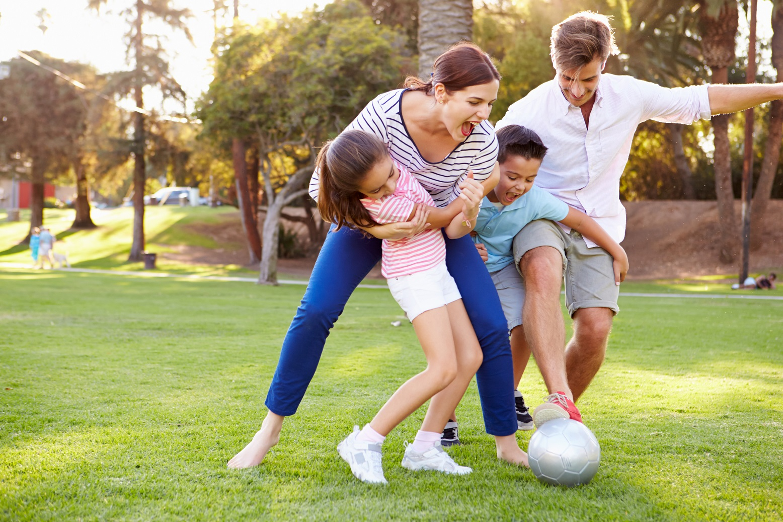 Young family playing soccer on a field