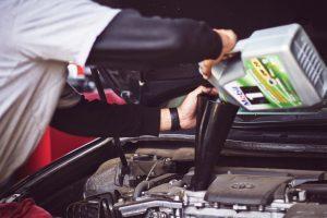 Man putting oil in car