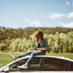 Young woman sitting on the roof of a car